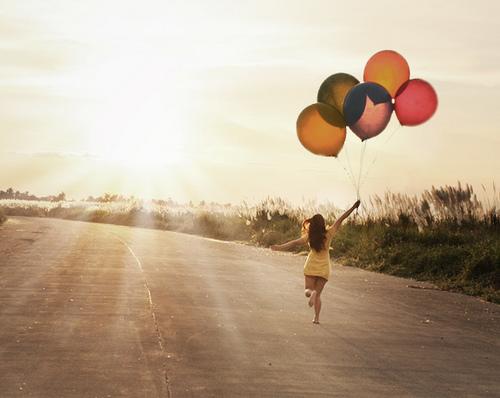 garota correndo com balões
